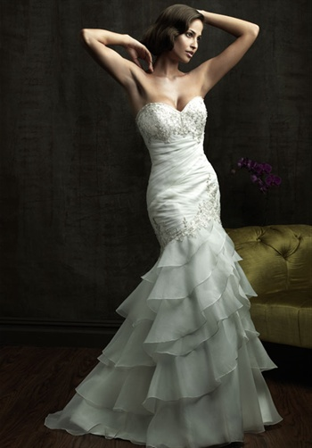 Gown features beading, ruching, ruffled skirt, and Swarovski crystals.
